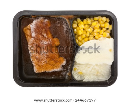 An overhead view of a frozen prepared pork and vegetable TV dinner. - stock photo