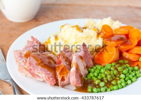 An overhead view of a roast gammon dinner on a white plate with a gravy boat in the background - stock photo
