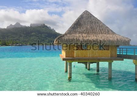 An overwater bungalow above the lagoon in Bora Bora, Tahiti. - stock photo