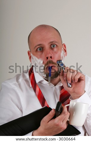 An overworked man doing many things at once with a funny expression - stock photo