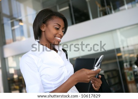An pretty african american business woman checking her cell phone - stock photo