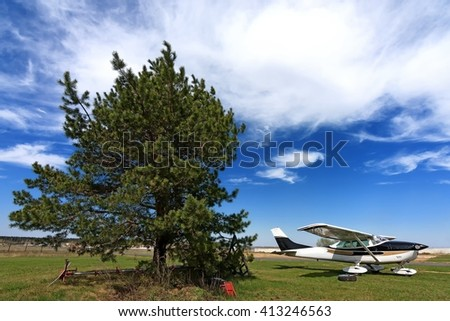 An small single propeller engine aircraft and pine tree against bright scenic sky with high clouds - stock photo