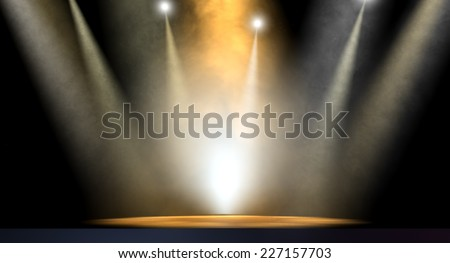 An stage lit by an array of spotlights on a dark background - stock photo