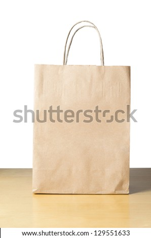 An unbranded brown paper carrier bag with twisted handles on a light wood table with white background, facing front with empty space for text. - stock photo