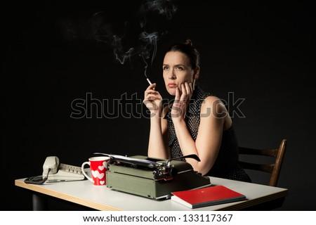 An unhappy woman in a retro work desk - stock photo