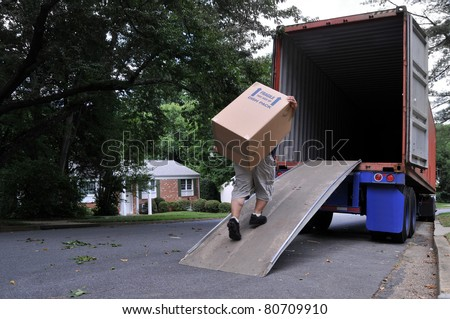 An unidentifiable person is carrying a heavy moving box up a ramp into the back of a moving truck (altered features, not recognizable), on a summer day in typical suburban America - stock photo