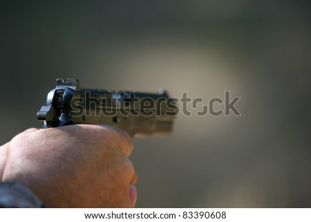 an unidentifiable person shoots a high power pistol. low depth of field photo so the background in out of focus and focus is on the gun - stock photo