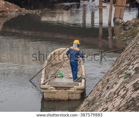 An unidentified female worker is cleaning a polluted canal. It is full of dark water and many kinds of wastes. Pollution is one of the most serious problem of Vietnam. Environmental protection concept - stock photo