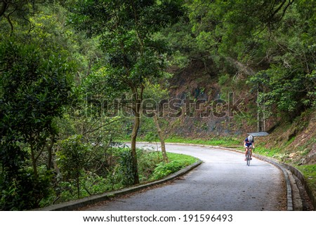 An Unidentified Man Cycling in Famous MacLehose Trail Section 9 in Hong Kong, China  - stock photo