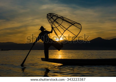 An unknown fishermen at Myanmar's Inle Lake strikes a pose in front of the sun - stock photo