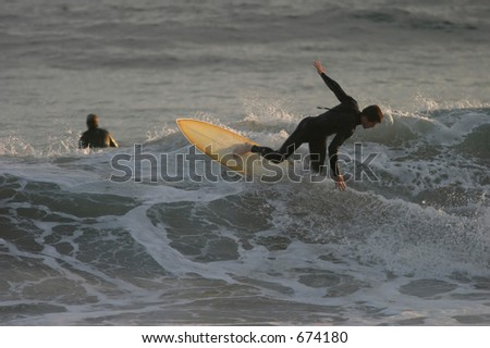 An unknown surfer rides the waves in Malibu. - stock photo