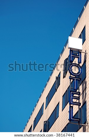 An unlit neon hotel sign situated next to the room windows - stock photo