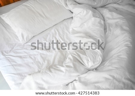 An unmade bed with crumpled bed sheet, a blanket and pillows after waking up in the morning. - stock photo