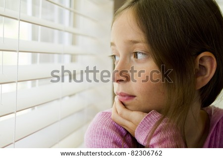 An unsmiling young girl gazes through window blinds. - stock photo
