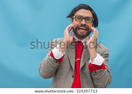 An untidy man, wearing broken glasses, expressing horror, over light blue background - stock photo