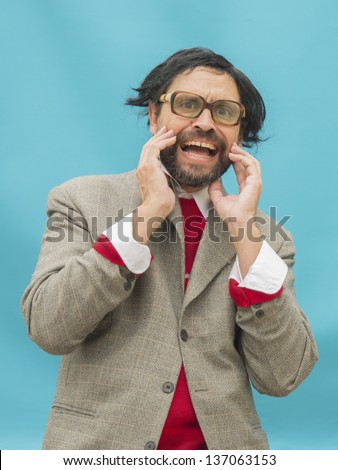 An untidy man, wearing glasses, expressing horror, over light blue background - stock photo