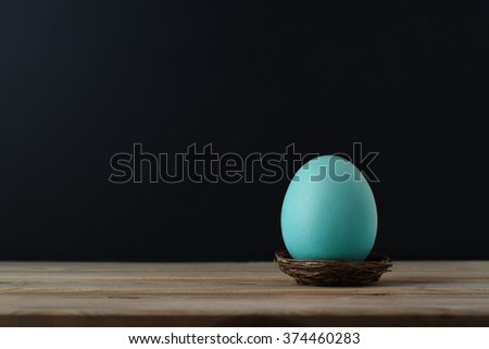 An upright chicken's egg, tinted turquoise blue in small nest on wood plank table.  Black chalkboard background provides copy space. - stock photo
