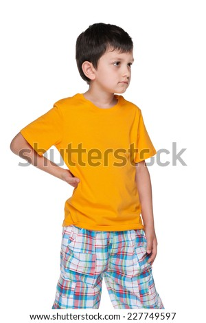 An upset boy in a yellow shirt is standing against the white background - stock photo