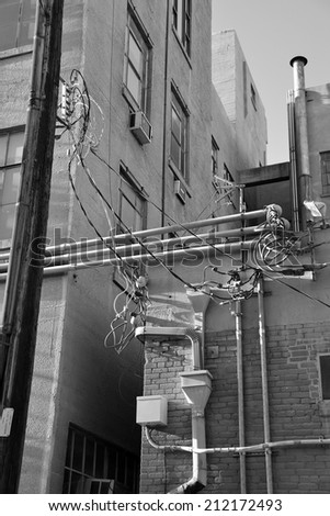 An urban alley shows electronic and electrical modifications made over the years resulting in a tangle of exposed conduit, wiring, junction boxes and splices. - stock photo