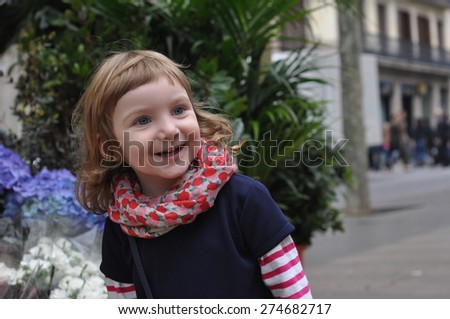 An urban portrait of a stylish baby girl in a red scarf - stock photo