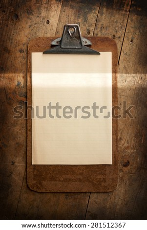 An vintage clipboard on a old wooden desk, with blank paper. intentionally shot with a beam of horizontal light (highlighting) to emphasize your message (to be inserted).  - stock photo