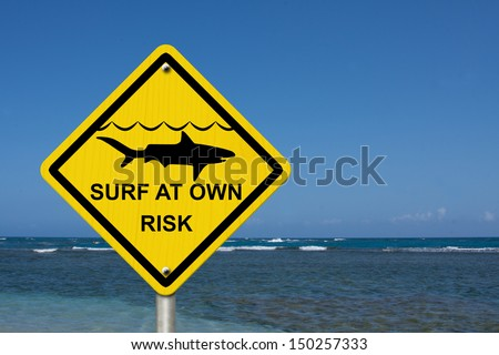 An warning sign at the beach with shark symbol and words surf at own risk, Use caution when surfing because sharks are present - stock photo