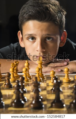 An 11 year old boy thinking about his next move during a chess game.  - stock photo