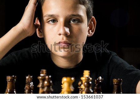 An 11 year old boy thinks about his next move during a chess game.  - stock photo