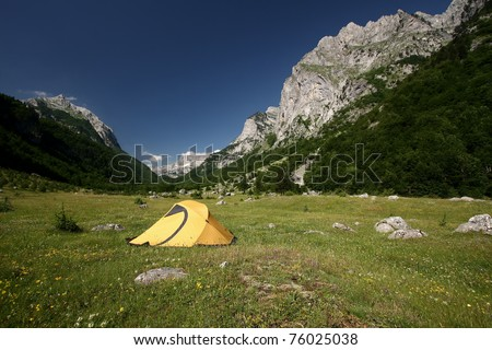 an yellow tent on a green meadow at the foot of a mountain. Ropojana Valley, Prokletije Mountains, or Albanian Alps, Montenegro - stock photo