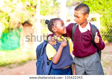 an young african brother with his arm around his younger sister showing positivity with a thumbs up while his younger sister looks up at him in adoration and pride - stock photo