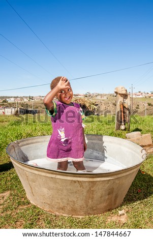 an young african girl playing happily in the outdoors in a big corrugated iron bucket used for laundry - stock photo
