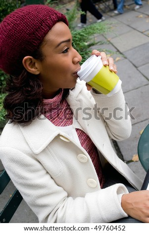 An young business woman takes a sip of her hot coffee or other beverage. - stock photo