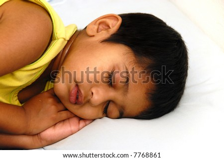 An young kid lying in bed feeling very sick - stock photo