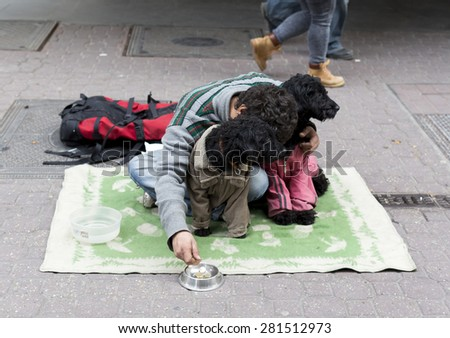 An young man is begging on the ground of a main street in Budapest, Hungary. - stock photo
