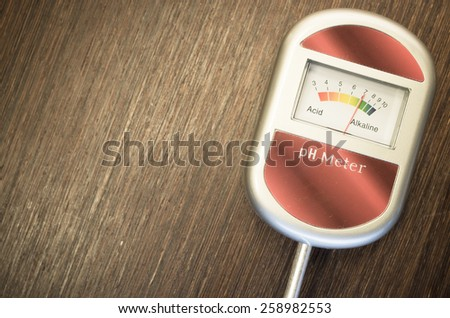 analog tool to measure soil ph on a dark wood background - stock photo