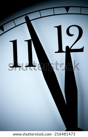 Analog wall clock in a low light with black hands and numbers with few minutes left to 12 hour. Concept image of time,the past or deadline. - stock photo