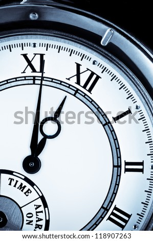 Analog wrist watch closeup at five to twelve - stock photo