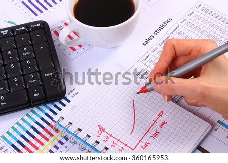 Analysis of sales plan, computer keyboard and cup of coffee on financial chart, business report, business work station with paperwork - stock photo