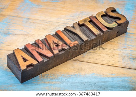 analytics word typography - text in vintage letterpress wood type against grunge painted  wood - stock photo