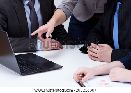 Analyzing computer data on business meeting, close-up - stock photo