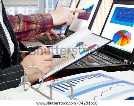 Analyzing data and charts in the office - stock photo