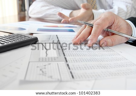 Analyzing Data.  Closeup of hands with financial  charts  at business meeting in the office - stock photo