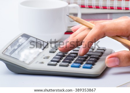 Analyzing numbers and doing calculations at the office - stock photo