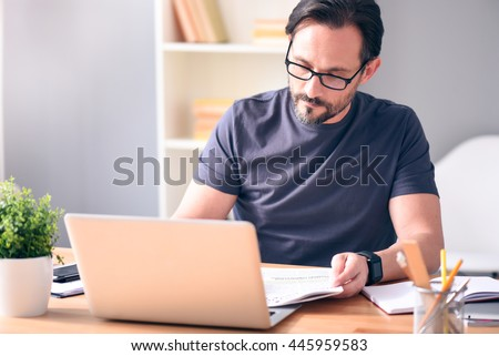 Analyzing the situation. Serious mature bearded man with glasses looking at newspaper while sitting in front of the laptop at the table - stock photo