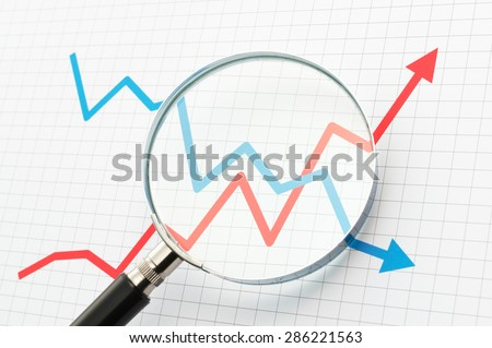 Analyzing upside growing and downside declining arrows chart with magnifying glass. Line graph and magnifying glass. Watching moves.   - stock photo