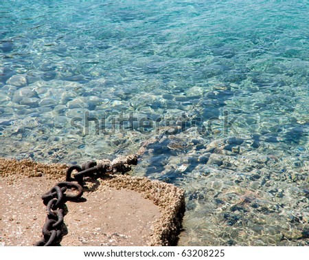 Anchor chain leaving in the sea - stock photo