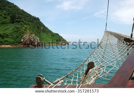 Anchor on vintage wooden sailing ship on blue tropical ocean  View at green mountains in caribbean sea in Buzios Brazil sailing on a sunny day in summer - stock photo