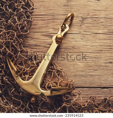 Anchor on wood background - stock photo