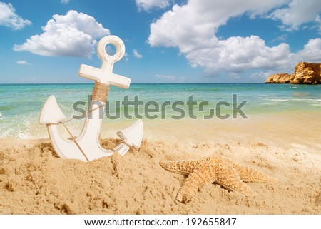 Anchor with starfish on a sandy beach - summer holiday concept - stock photo
