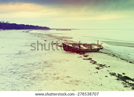 Anchored fishing boat on sandy beach of the Baltic Sea. Image toned in vintage warm colors style - stock photo